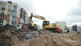 Dolly shot slowmotion excavator dig soil and dump it in truck at building site stock video footage