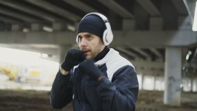 Dolly shot of sportive man boxer in headphones training punches in urban location outdoors in winter stock video footage