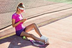 Dolly shot of sporty girl sitting on a tennis court near net and uses smart phone for chatting and surfing on social. Dolly shot of cute sporty girl sitting on a royalty free stock photos
