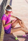 Dolly shot of sporty girl sitting on a tennis court near net and uses smart phone for chatting and surfing on social. Dolly shot of cute sporty girl sitting on a stock images
