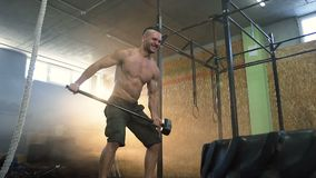 Dolly shot of strong fit man beatting tractor ride using hammer during crossfit training at gym. stock footage