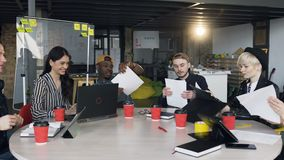 Team of young hipster working together on the new business plan. Dolly shot of team of young hipster people in stylish casual clothes working together on the stock video