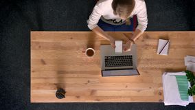 Dolly shot of top down view of casually-dressed woman working with smartphone in office in front of the laptop. Dolly shot of top down view of casually-dressed stock footage