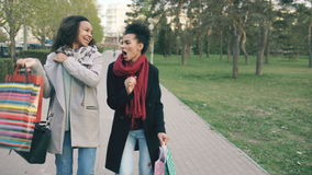 Dolly shot of two attractive mixed race women dancing and have fun while walking down the park with shopping bags. Happy stock footage