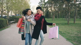 Dolly shot of two attractive mixed race women dancing and have fun while walking down the park with shopping bags. Happy. Dolly shot of two attractive mixed race stock footage