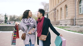 Dolly shot of two attractive mixed race women dancing and have fun while walking down the street with shopping bags. Happy young friends walk after visiting stock footage