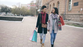 Dolly shot of two attractive mixed race women with shopping bags enjoying their walk down the street. Girlfriends have stock video footage
