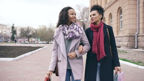 Dolly shot of two attractive mixed race women with shopping bags talking and walking down the street. Girlfriends have. Fun after visiting mall stock footage