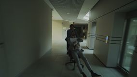 Dolly shot of Two crazy businessmen riding office chair and throwing papers up while having fun in lobby of modern. Business center indoors stock video