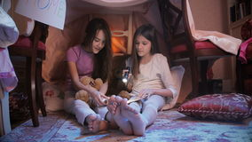 Dolly shot of two girls reading book in tepee tent in bedroom at night stock footage