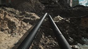 Dolly shot two long black plastic tubes laying in a ditch at building site stock video footage
