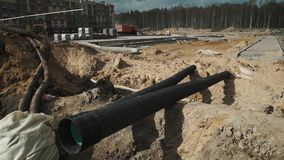 Dolly shot two long black plastic tubes laying in trench at building site stock footage