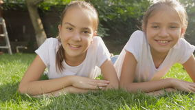 Dolly shot of two smiling girls lying on grass at park stock video footage