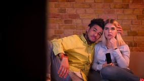 Dolly shot of young african guy hugging his blonde caucasian girlfriend watching sad movie at home. stock footage