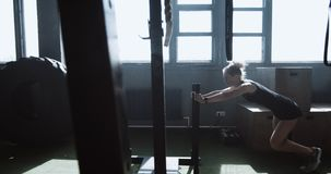 Dolly shot young athletic blonde woman working out with functional training sled in big atmospheric gym slow motion. Determination and willpower, professional stock video footage