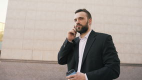 Dolly shot of young bearded business man talking at smartphone with cup of coffee near modern office buildings stock footage