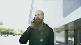 Dolly shot of young bearded hipster man concentrated talking on phone on citystreet, conversation near office building stock footage