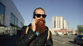 Dolly shot of young bearded hipster man in sunglasses smiling and talking smartphone while travelling city street