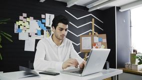 Dolly shot of young businessman typing on his laptop keyboard in a loft office stock video footage