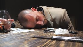 Dolly shot of young drug dealer unconscious lying after heroin dose on the table. Male addict passed out after cocaine. Overdose on the desk. Addiction and stock video footage