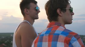 Dolly shot of young male couple in sunglasses standing on the edge of rooftop and talking. Handsome gay boys rest on. Roof of high-rise building and enjoying stock video
