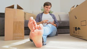 Dolly shot of young man sitting on floor surrounded by carton boxes and using digital tablet stock video