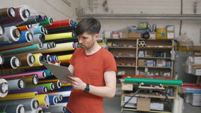 Dolly shot of Young worker in warehouse with clipboard checking inventory. Man works in sales department of advertising