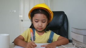 Dolly Slider Asian little girl with yellow engineer cap drawing on white paper stock footage