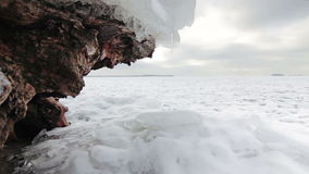 DOLLY: Stone covered with snow on the shore of a frozen lake. DOLLY: Stone (old snag) covered with snow on the shore of a frozen lake stock footage