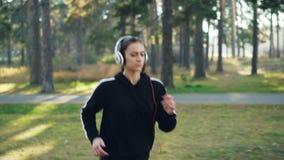 Dolly strzał jogging w parku i słuchaniu radio w hełmofonach ćwiczy samotnie śliczna brunetka nowoczesna technologia zbiory