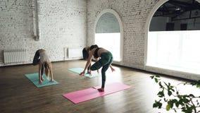 Dolly strzał młode kobiety ćwiczy joga robi przednim chył pozom na jaskrawych matach kłama na drewnianej podłoga w lekkim studiu zbiory