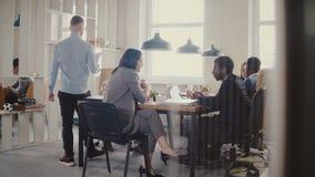 Dolly strzał praca zespołowa przy loft biura nowożytnym stołem Wieloetniczni ludzie biznesu współpracują, dyskutują rynek przy sp zbiory