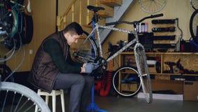 Dolly strzał skupiający się młody machanic naprawianie łamający roweru pedała obsiadanie na stolec blisko nowożytnego bicyklu w m zbiory wideo