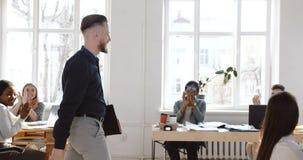 Dolly strzał szczęśliwy uśmiechnięty w średnim wieku męski szef wchodzić do nowożytnego biuro, koledzy rozwesela on w górę i klas zbiory wideo