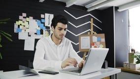 Dolly strzelał młody biznesmen pisać na maszynie na jego laptop klawiaturze w loft biurze zdjęcie wideo
