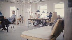 Dolly strzelał przypadkowi wieloetniczni urzędnicy cieszy się zdrową biurową atmosferę Praca zespołowa, widok przez szklanej ścia zdjęcie wideo