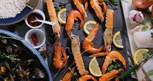 Dolly top down mening van ingrediënt voor een Spaanse zeevruchtenpaella: mosselen, koningsgarnalen, langoustine stock videobeelden