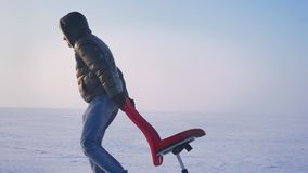 Dolly wide shot of sportsman in warm coat and hood pulling slowly a red chair along the snowy field. Dolly wide shot of sportsman in warm coat and hood pulling stock video footage