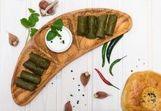 Dolma στο ξύλινο πιάτο με τα καυτά πιπέρια, το σκόρδο, τη μέντα και την ξινή κρέμα στην άσπρη τοπ άποψη υποβάθρου Στοκ Εικόνες