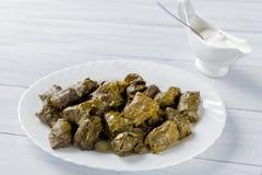 Dolma välfyllt kött i druvasidor på den vita plattan och bunken med kräm- sås på den vita trätabellen Royaltyfria Bilder