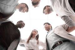 Dolny widok biznesowi drużyna stojaki wpólnie, tworzący okrąg fotografia royalty free