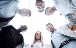 Dolny widok grupa młodzi ludzie stoi wpólnie, tworzący okrąg zdjęcia royalty free