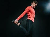 Dolny widok młody Europejski mężczyzna jest ubranym czerwonego sportswear i rozciąga jego po ciężkiego treningu w ciemnym tle nog Zdjęcia Stock
