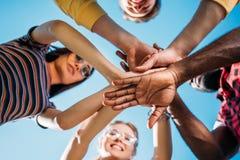 dolny widok multiracial młodzi przyjaciele trzyma ręki wraz z niebieskim niebem obrazy stock