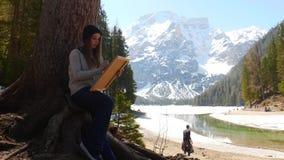 Dolom?as Una mujer joven que dibuja en una lona en naturaleza almacen de metraje de vídeo
