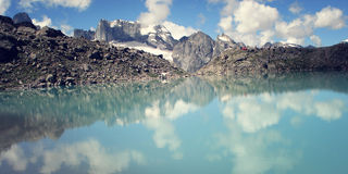 Dolomite Lake at Uzunkol, Caucasus Mountains. Bright blue alpine lake. Bright blue alpine lake. View of Distant Peaks. Retro filter photo. Cloud reflections at Stock Photography