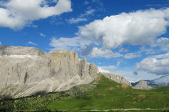 Dolomite peaks above green hill Stock Photos