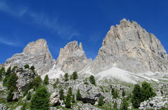 Dolomite peaks Sassolungo above green hill Stock Image