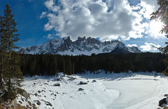 Dolomites caress frozen lake. Snowy landscape and icy lake in the dolomites Stock Photos