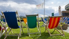 Dolomites, Italy. Group of colored deckchairs outside the mountain lodge in summer time stock photo